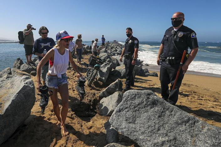 Newport Beach police officers enforce beach closure at the Wedge.