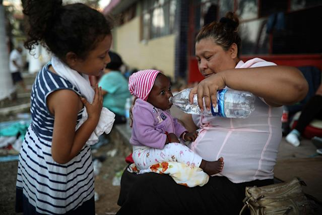 <p>A Central American migrant woman gives water to a baby as the annual Migrant Stations of the Cross caravan sets up camp for a few days at a sports center in Matias Romero, Oaxaca state, Mexico, late Monday, April 2, 2018. (Photo: Felix Marquez/AP) </p>