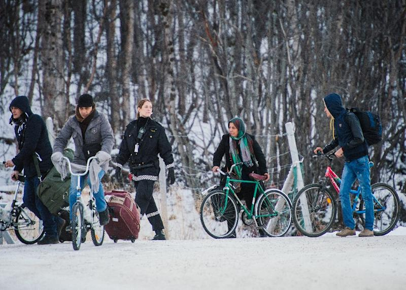 Refugees walk alongside bikes to the Norwegian border crossing station at Storskog after crossing the border from Russia on November 12, 2015