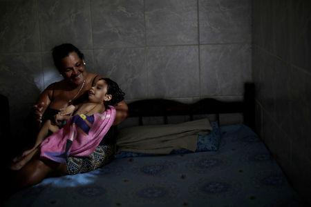 """Silvina da Silva poses with her two-year-old granddaughter Ana Sophia, who was born with microcephaly, at their house in Olinda, Brazil, August 7, 2018. Ana Sophia's mother Gabriela had planned to finish high school and study physical therapy. Now, she spends her days caring for her child. Her husband left shortly after Ana Sophia's birth. He could not accept their child's condition, Gabriela says, and does not pay child support. """"I went into depression and my family helped me,"""" she said. """"If it was not for them, I would have gone crazy."""" Today, some relatives give moral support and Ana Sophia's paternal grandmother helps with her day-to-day care. REUTERS/Ueslei Marcelino/Files"""