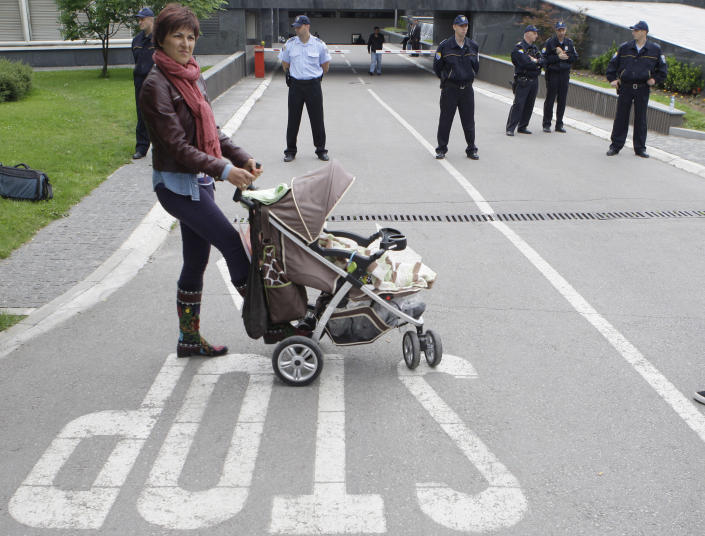 Bosnian woman Selma Zatega , with her baby Luna takes part protest in front of the Bosnian parliament building in Sarajevo, on Wednesday, June 5, 2013. Dozens of people are blocking the entrance to Bosnia's Parliament demanding lawmakers to pass a new law on personal identification numbers after the old one came out of force in February, leaving all babies born since then without personal documents. Bosniak, Serb and Croat lawmakers can't agree about the territorial regions that would issue the numbers. The result is depriving newborns the ID numbers needed to get health insurance or a passport. (AP Photo/Amel Emric)