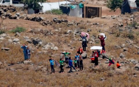 Some of the Syrians waved white clothes across the border - Credit: AFP