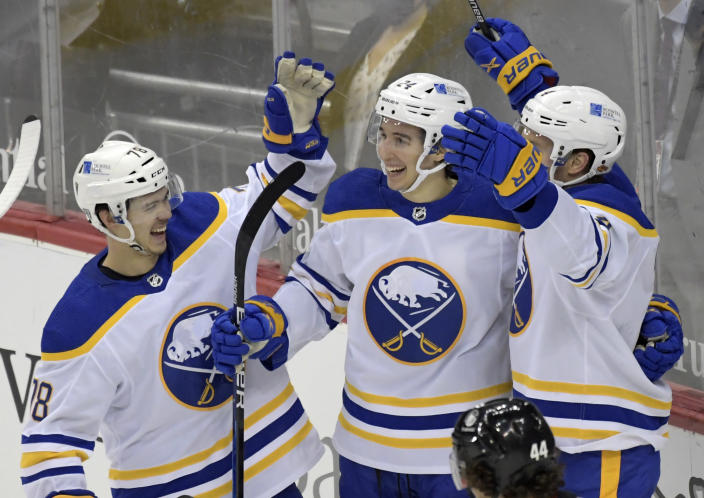Buffalo Sabres center Dylan Cozens (24) celebrates his goal with Buffalo Sabres' Jacob Bryson, left, and Taylor Hall (4) during the third period of an NHL hockey game against the New Jersey Devils Tuesday, Feb. 23, 2021, in Newark, N.J. The Sabres won 4-1.(AP Photo/Bill Kostroun)