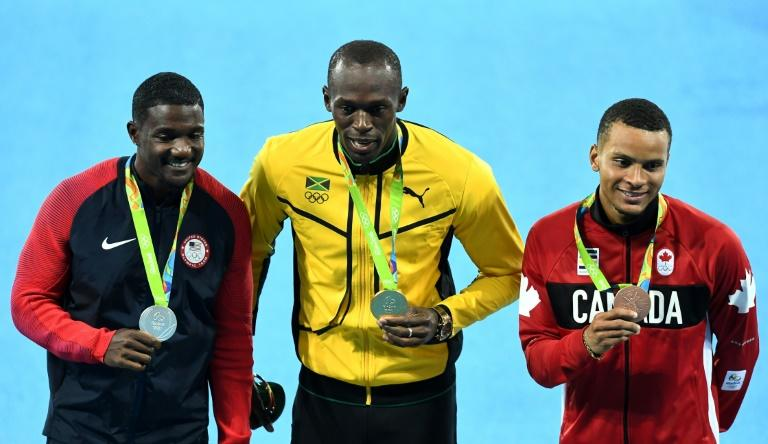 Gold medallist Jamaica's Usain Bolt (C) poses with silver medallist USA's Justin Gatlin (L) and bronze medallist Canada's Andre De Grasse after the athletics 100m final during the Rio Olympic Games, in August 2016