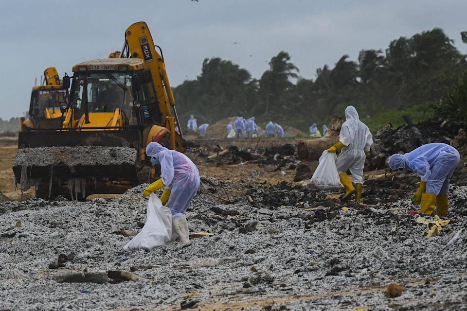 <p>Sri Lankan Navy soldiers with the help of heavy machinery work to remove debris washed ashore from the Singapore-registered container ship MV X-Press Pearl, which has been burning for the eighth consecutive day in the sea off Sri Lanka's Colombo Harbour, on a beach in Colombo on May 28, 2021. </p> (AFP via Getty Images)