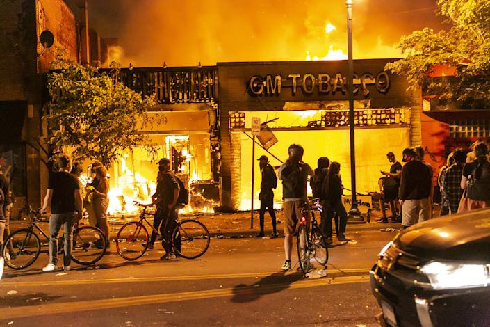Protestors set a shop on fire on Thursday, May 28, 2020, during the third day of protests over the death of George Floyd in Minneapolis. Floyd died in police custody in Minneapolis on Monday night, after an officer held his knee into Floyd's neck for more than 5 minutes. (Jordan Strowder/Anadolu Agency via Getty Images)