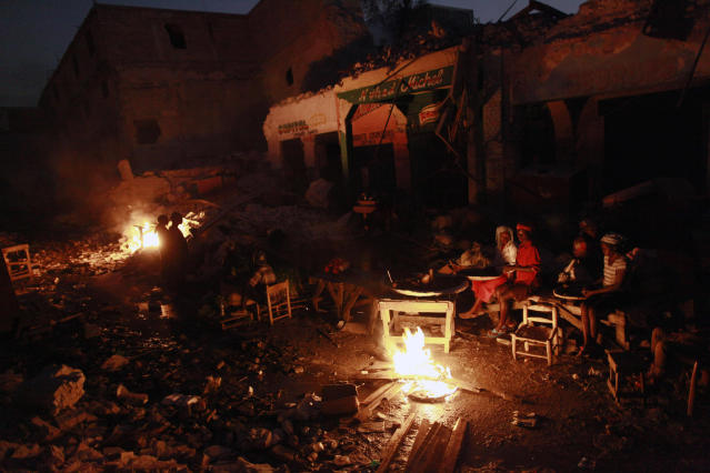 <p>Earthquake survivors sit around a fire in downtown Port-au-Prince, Friday, Feb. 5, 2010. (Photo: Rodrigo Abd/AP) </p>
