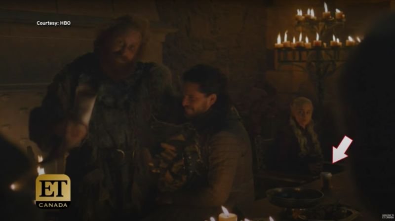 A scene from Game of Thrones in which a coffee cup is visible in the background