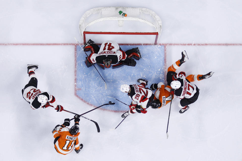 Philadelphia Flyers' Travis Konecny (11) tries to get a shot past New Jersey Devils' Scott Wedgewood (41), Ryan Murray (22) and Damon Severson (28) as Yegor Sharangovich (17) defends against Sean Couturier (14) during the second period of an NHL hockey game, Monday, May 10, 2021, in Philadelphia. (AP Photo/Matt Slocum)