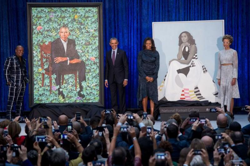 The Obamas (middle) stand in front of their Smithsonian portraits, painted by Kehinde Wiley (left) and Amy Sherald (right)