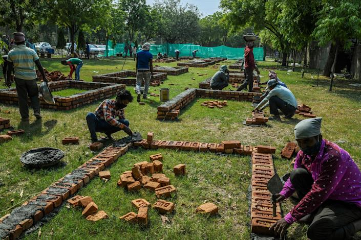 "Workers build new platforms to expand a mass cremation site in New Delhi on April 27.<span class=""copyright"">Atul Loke—The New York Times/Redux</span>"