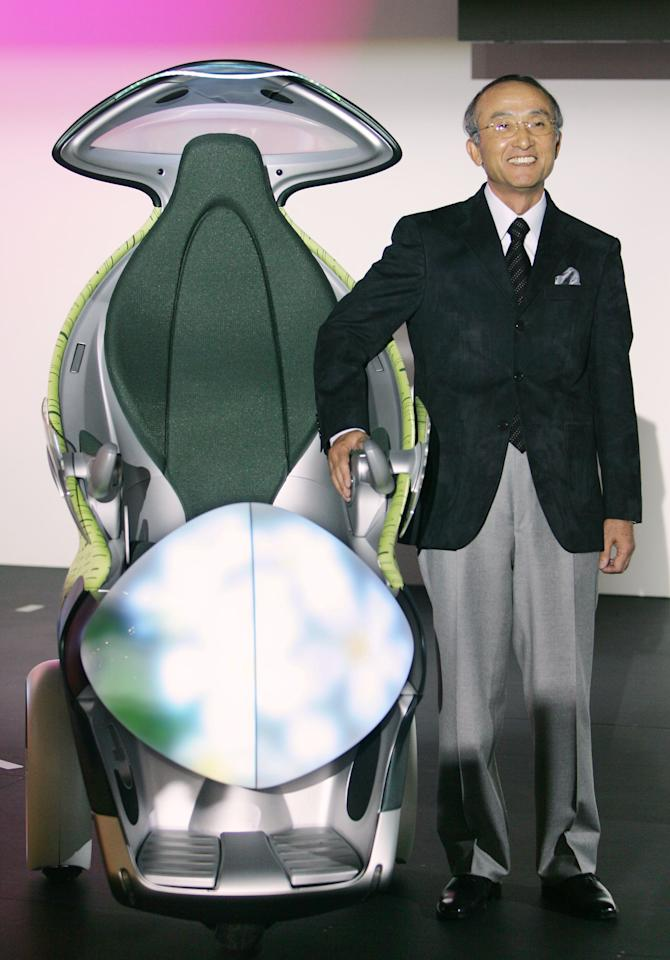 """Japan's auto giant Toyota president Katsuaki Watanabe stands next to its concept car """"i-swing"""", a persoanl mobility vehicle, at the 39th Tokyo Motor Show in Makuhari, 19 October 2005. Toyota has plans to exhibit seven Toyota-brand concept vehicles and 16 production vehicles.  AFP PHOTO/Kazuhiro NOGI"""