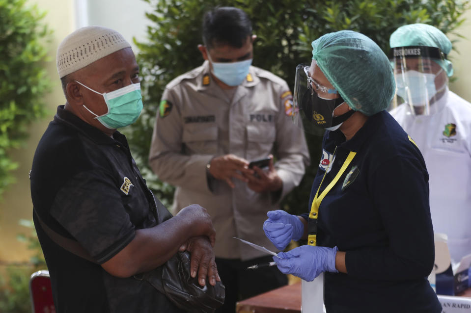 A relative of a passenger of a Sriwijaya Air jet that crashed into the sea, talks to a members of Disaster Victim Identification (DVI) team at a hospital in Jakarta, Indonesia, Tuesday, Jan. 12, 2021. Indonesian navy divers were searching through plane debris and seabed mud Tuesday looking for the black boxes of the jet that nosedived into the Java Sea over the weekend with 62 people aboard. (AP Photo/Achmad Ibrahim)
