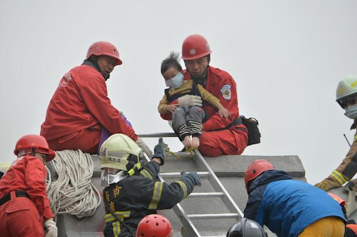 Rescue personnel help a young victim at the site of a collapsed building in the southern Taiwanese city of Tainan following a strong 6.4-magnitude earthquake that struck the island early on February 6, 2016 (AFP Photo/)