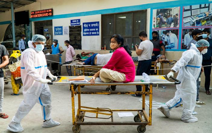 Hospital staff transports a coronavirus patient in a hospital complex in New Delhi - AFP
