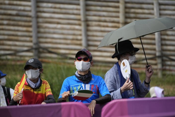 Supporters use fans to beat the heat at the men's cross country mountain biking at the 2020 Summer Olympics, Monday, July 26, 2021, in Izu, Japan. (AP Photo/Christophe Ena)