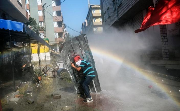 A protester shields himself from water cannons during clashes with Turkish police officers on July 26, 2015 in Istanbul (AFP Photo/Bulent Kilic)