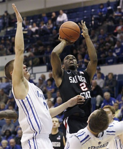 San Diego State guard Xavier Thames, right, goes up for a shot as Air Force forwards Marek Olesinski, front left, and Mike Fitzgerald cover in the first half of an NCAA basketball game at Air Force Academy, Colo., on Saturday, Feb. 18, 2012. (AP Photo/David Zalubowski)