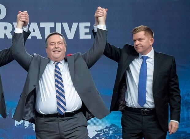 Jason Kenney celebrates his 2017 victory as the first official leader of the Alberta United Conservative Party with his opponent, Brian Jean, at right.