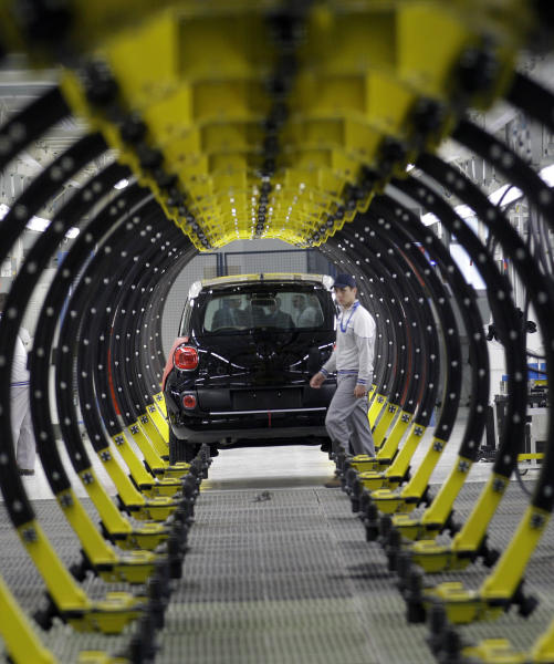 A Serbian factory worker looks at a Fiat 500 L car in the assembly hall in the new Fiat factory, in Kragujevac, some 100 kilometers (70 miles) south of Belgrade, Serbia, Monday, April 16, 2012. Italian carmaker Fiat has opened a production line in Serbia for its new 500L family model, to expand on the popularity of its two-door 500 city car. Fiat hopes to sell about 160,000 hatchbacks a year produced in this central Serbian town, to take advantage of low wages, tax breaks and government subsidies. (AP Photo/Darko Vojinovic)