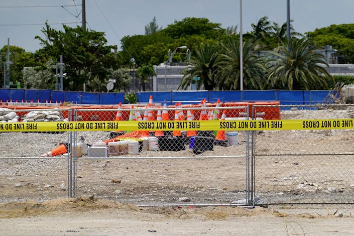 Fire department tape keeps people out of the empty lot where the collapsed 12-story Champlain Towers South condo building once stood on July 27, 2021 in Surfside, Florida.