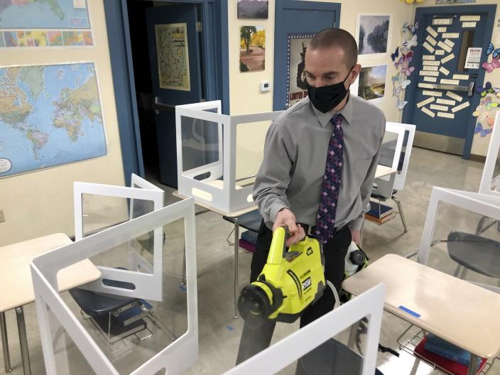 Assistant Principal Mike Saisi disinfects desks at the Sinaloa Middle School in Novato, Calif. on Tuesday, March 2, 2021. The school reopened Monday, Feb. 22, 2021 for in-person learning. (AP Photo/Haven Daily)