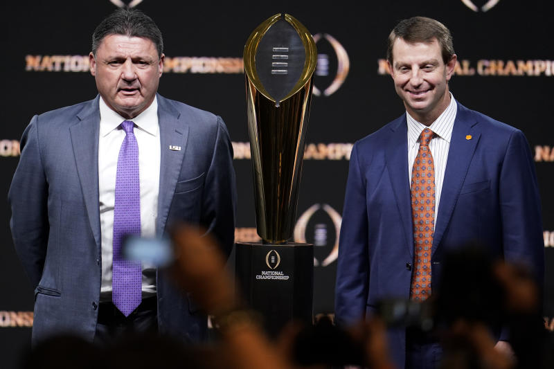 LSU's Ed Orgeron (L) and Clemson's Dabo Swinney pose with the trophy after a news conference before the 2020 college football title game. (AP)
