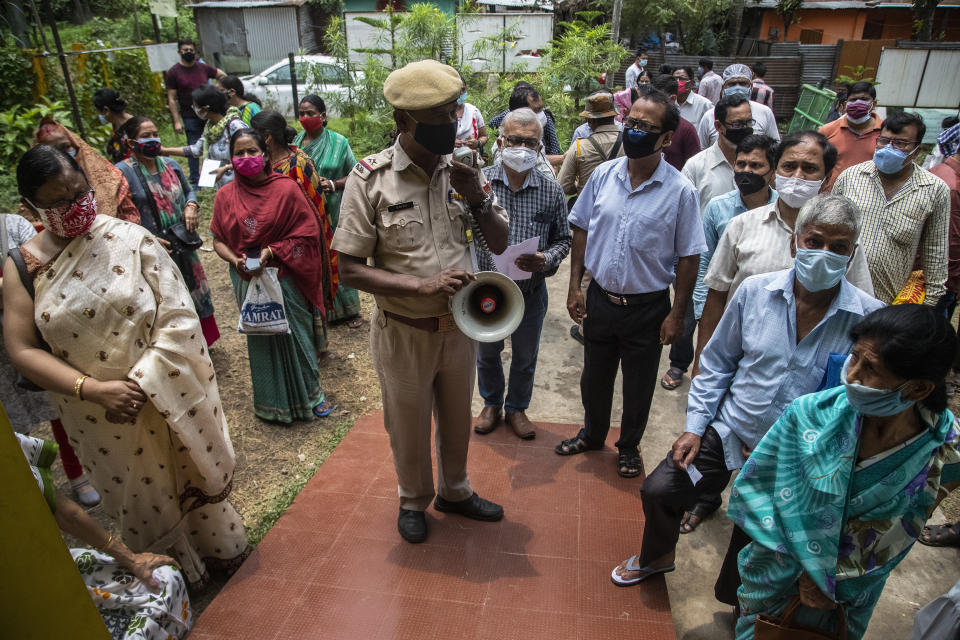 A police officer uses a loudspeaker to address the people who have come to receive COVID-19 vaccine at a government run hospital in Gauhati, India, Saturday, May 8, 2021. Infections have swelled in India since February in a disastrous turn blamed on more contagious variants as well as government decisions to allow massive crowds to gather for religious festivals and political rallies. (AP Photo/Anupam Nath)