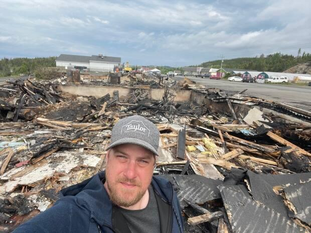 Mike McDonald, owner of 618 Entertainment Inc., stands over what used to be his studio. The studio was destroyed in a fire Friday night. (Submitted by Mike McDonald - image credit)