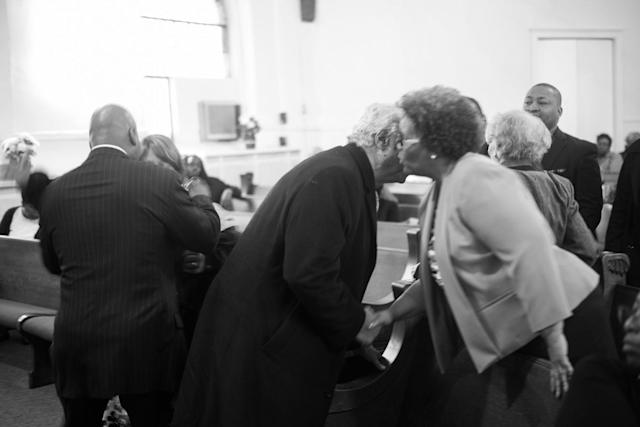 <p>Spencer Leak greets membres of a family at a funeral he helped organize on Chicago's south side. (Photo: Jon Lowenstein/NOOR for Yahoo News) </p>