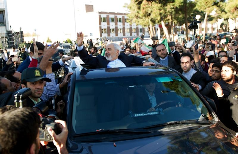 Iranian Foreign Minister Mohammad Javad Zarif (C) greets people as the nuclear negotiating committee arrive at Mehr Abad Airport in Tehran on April 3, 2015 (AFP Photo/Borna Ghasemi)