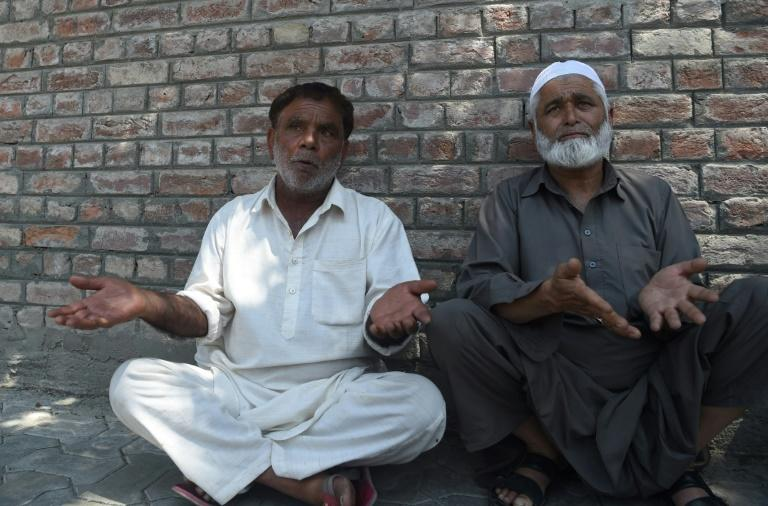 Two Kashmiri men wait outside a police station in Srinagar for news of relatives they say were detained by authorities (AFP Photo/PUNIT PARANJPE)