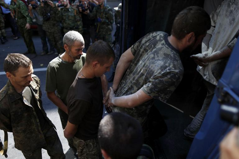Captured Ukrainian soldiers board a vehicle on August 24, 2014 in Donetsk, eastern Ukraine, during a parade in mockery of the country's Independence Day celebrations