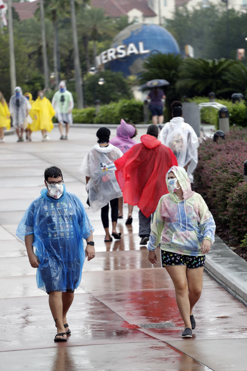In this Wednesday, June 3, 2020 photo, guests brave a rainy day at Universal Studios Wednesday, June 3, 2020, in Orlando, Fla. The Universal Studios theme park has reopened for season pass holders and will open to the general public on Friday, June 5. (AP Photo/John Raoux)