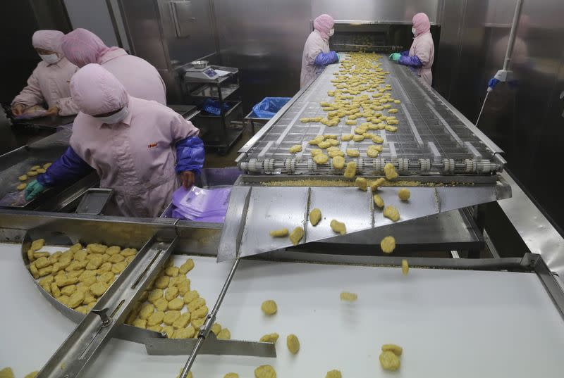 Employees work at a production line prior to a seizure at the Husi Food factory in Shanghai