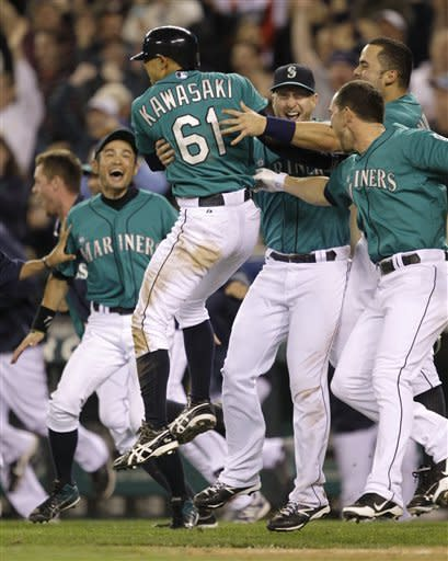 Seattle Mariners' Munenori Kawasaki (61) is mobbed by teammates after he scored the winning run against the Detroit Tigers in a baseball game, Monday, May 7, 2012, in Seattle. The Mariners beat the Tigers, 3-2. (AP Photo/Ted S. Warren)