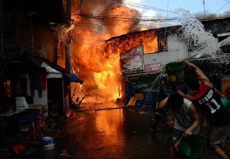 Residents try to put out a fire in a house in a shanty town in Manila on December 4, 2015 (AFP Photo/Ted Aljibe)