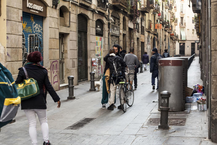 A young couple kisses in the middle of a group of people , Barcelona, Spain, Thursday, March 19, 2020. (José Colon for Yahoo News)