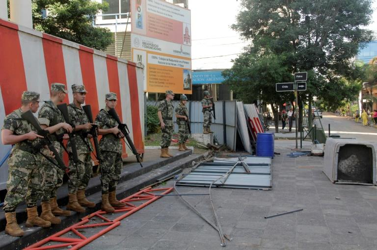 Police guard the area around Government House in Asuncion, after demonstrators set fire to the Congress building during protests over a constitutional amendment