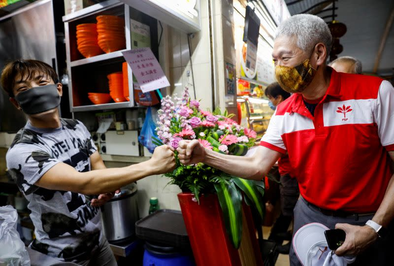 Lee Hsien Yang of the Progress Singapore Party (PSP) greets a hawker during a walkabout ahead of the general election in Singapore