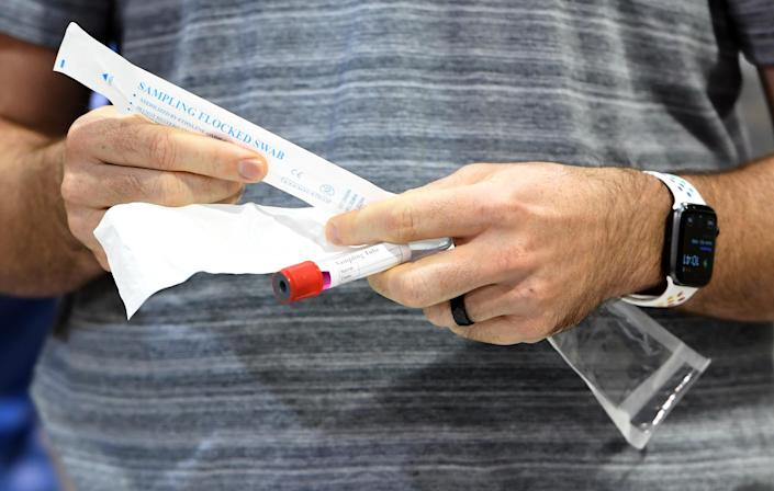 Nathanael Carlson of Nevada opens a coronavirus test kit during a preview of a COVID-19 testing site in Las Vegas. (Ethan Miller/Getty Images)