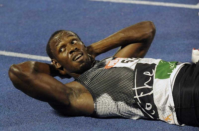 World-record holder Usain Bolt looks at the crowd while getting his right hamstring stretched out after loosing to fellow country man Yohan Blake in the 200m final at Jamaica's Olympic trials in Kingston, Jamaica, Sunday, July 1, 2012. Blake edged Bolt by 0.03 finishing in 19.80 seconds. (AP Photo/Collin Reid)