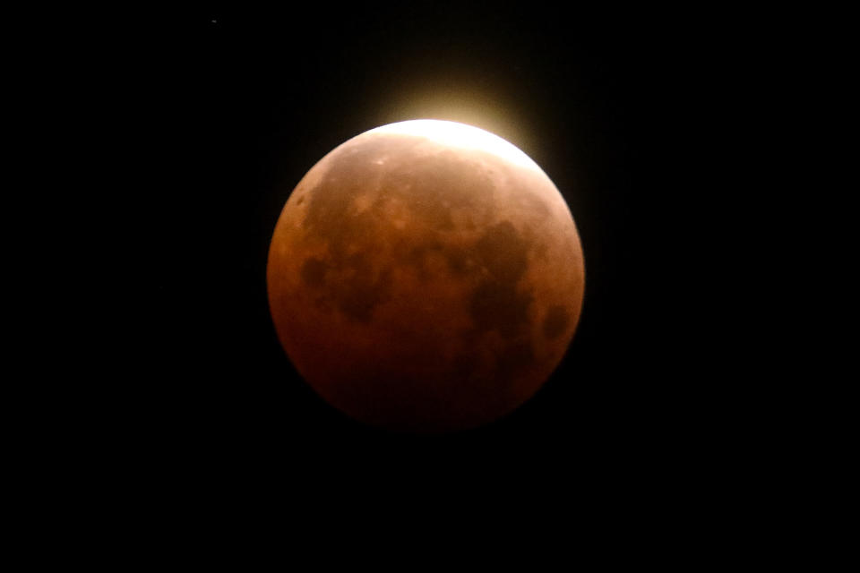 A total lunar eclipse is seen over Santa Monica Beach in Santa Monica, Calif., Wednesday, May 26, 2021. The first total lunar eclipse in more than two years is coinciding with a supermoon for quite a cosmic show. (AP Photo/Ringo H.W. Chiu)