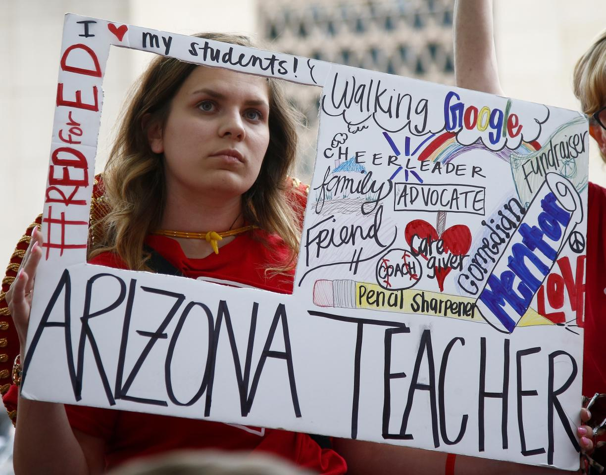 <p>Teacher Taylor Dutro listens as protest organizers announce Arizona teachers intentions to go back to work if lawmakers pass a school funding plan, during the fourth day of the statewide teachers' strike at the Arizona Capitol Tuesday, May 1, 2018, in Phoenix. (Photo: Ross D. Franklin/AP) </p>