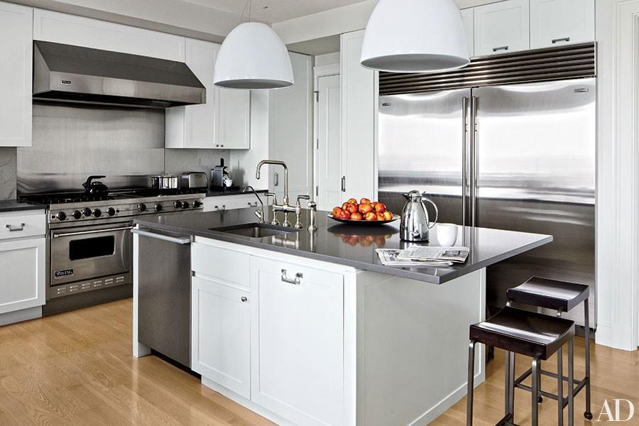 """Domed pendant lights by Artemide hang above a Caesarstone-topped island in a <a rel=""""nofollow"""" href=""""http://www.architecturaldigest.com/story/victoria-hagan-milwaukee-lake-michigan-home-article?mbid=synd_yahoo_rss"""">Milwaukee high-rise apartment</a>'s kitchen designed by Victoria Hagan."""