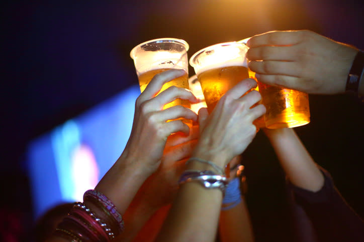 A file photo of a group of people holding up cups of beer. Dozens of people at a Schofields party in Sydney are expected to be fined for breaching coronavirus restrictions.