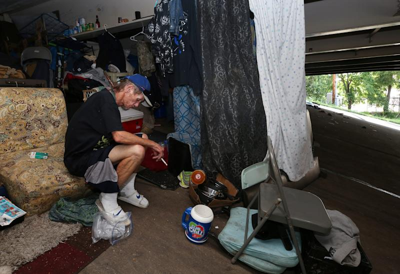 Brent Spradlin sits next to his makeshift tent in a homeless camp beneath the I-65 overpass at Brook and Breckinridge streets. Spradlin was stressed about moving from the camp after the city announced it would clear it. July 8, 2019