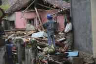 A man inspects his house damage at a tsunami-ravaged village in Sumur, Indonesia, Tuesday, Dec. 25, 2018. The Christmas holiday was somber with prayers for tsunami victims in the Indonesian region hit by waves that struck without warning Saturday night.(AP Photo/Tatan Syuflana)