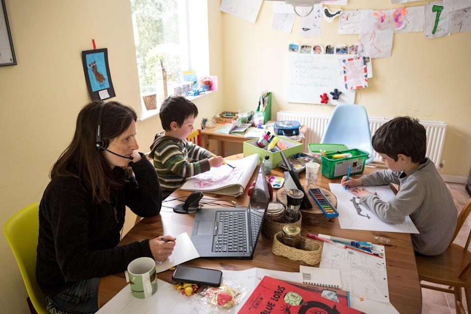 Six-year-old Leo (R) and his three-year old brother Espen (C) complete homeschooling activities suggested by the online learning website of their infant school, as his mother Moira, an employee of a regional council, works from home in the village of Marsden, near Huddersfield, northern England on May 15, 2020. (Photo by OLI SCARFF/AFP via Getty Images)