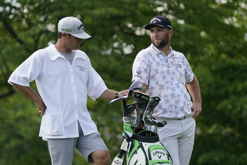 Jon Rahm talks with his caddie as he waits to hit on the 14th tee during the third round of the Memorial golf tournament, Saturday, June 5, 2021, in Dublin, Ohio. Rahm was later notified he tested positive for the coronavirus, knocking him out of the tournament. (AP Photo/Darron Cummings)